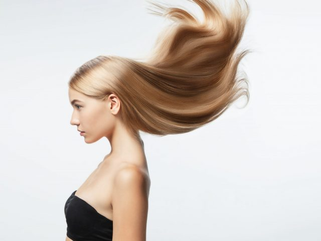 Beautiful model with long smooth, flying blonde hair isolated on white studio background. Young caucasian model with well-kept skin and hair blowing on air. Concept of salon care, beauty, fashion.